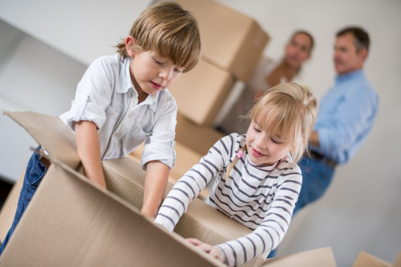 Family moving house and kids packing in boxes